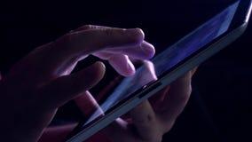 在片剂计算机的手势在暗室 紫色发光的触摸屏幕4K录影 股票视频