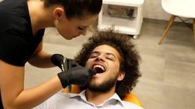 在牙医椅子的耐心开会和等待辅助的牙医确定他的牙的正确的树荫颜色 影视素材