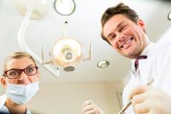 在牙科医生的处理从患者方面  免版税图库摄影