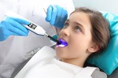 在牙齿办公室密封轻治疗,孩子 免版税图库摄影