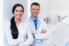 在牙齿诊所的牙医队 两位微笑的医生在他们的工作 免版税库存图片