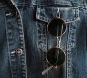 在牛仔布夹克的一个口袋的时髦葡萄酒圈子太阳镜 免版税库存照片