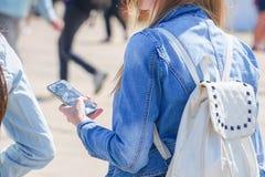 在牛仔布夹克的Ggirl拿着一个智能手机 免版税库存图片