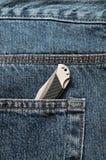 在牛仔布斜纹布的一个口袋的一把小折刀 免版税库存照片