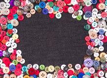 在牛仔布的多色的按钮 免版税库存照片