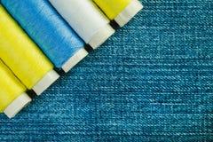 在牛仔布的行安排的蓝色,黄色和绿色缝合针线短管轴与拷贝空间 库存照片