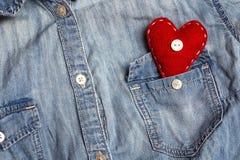 在牛仔布衬衣的口袋的红色心脏 库存图片