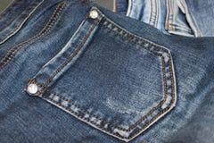 在牛仔布裤子、口袋和金属按钮的细节 免版税库存照片
