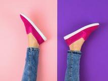 在牛仔裤和红色运动鞋的女孩` s腿在一个五颜六色的地板上 顶视图 库存图片