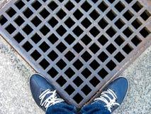 在牛仔裤和蓝色皮革运动鞋的人的腿在风暴流失的金属花格附近 滑稽的看法 r 免版税图库摄影