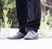 在牛仔裤和鞋子的男性腿 免版税库存照片