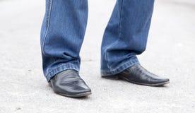 在牛仔裤和鞋子的男性腿 库存图片