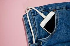 在牛仔裤的充电的电话 免版税库存图片