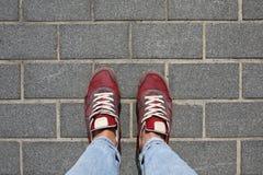 在牛仔裤的女性腿有在花岗岩路面的时兴的鞋子的 免版税库存图片