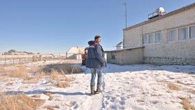在牛仔裤的走通过雪的一位男性研究员和一件温暖的制服之后在一冬天好日子在之间 股票录像