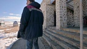在牛仔裤的走通过雪的一位男性研究员和一件温暖的制服之后在一冬天好日子在之间 股票视频