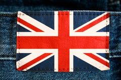 在牛仔裤皮革标签标记蓝色红色白色颜色的英国英国国旗在牛仔布背景 免版税库存照片