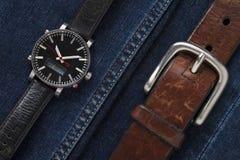 在牛仔裤织品的豪华手表与棕色皮带 库存图片
