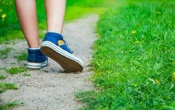 在牛仔裤运动鞋鞋子的走的妇女腿在路 免版税库存图片