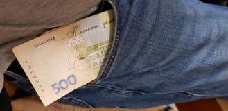 在牛仔裤长裤的一个口袋堆积的乌克兰金钱 库存图片