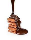 在牛奶巧克力片断倒黑暗的巧克力 免版税库存照片