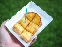 在牛奶浸入的面包,基于绿草的纸碟 库存照片