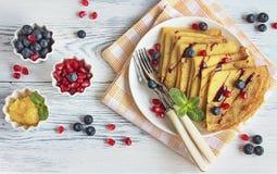 在牛奶的甜薄煎饼用蜂蜜和新鲜的莓果 免版税库存照片