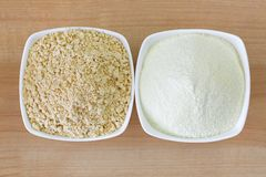 在牛奶粉末旁边的干大豆奶粉在白色碗,在木背景的顶视图 免版税库存图片