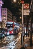 在牛津街,伦敦,英国的红色双层公共汽车接近的公交车站 免版税库存图片