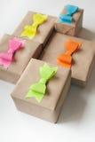 在牛皮纸包裹的礼物 色的明亮的纸弓 库存照片
