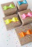 在牛皮纸包裹的礼物 色的明亮的纸弓 免版税图库摄影