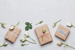 在牛皮纸和玫瑰色花或当前箱子包裹的礼物在灰色台式视图 平位置称呼 复制文本的空间 库存图片