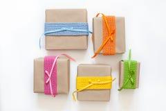在牛皮纸和磁带包裹的礼物从毛线编织了 免版税库存照片