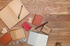 在牛皮纸和葡萄酒书的葡萄酒礼物在一张木桌上 免版税图库摄影