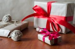 在牛皮纸的礼物与红色丝带 免版税图库摄影