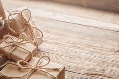 在牛皮纸的礼物盒与在木背景的弓 免版税图库摄影