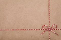在牛皮纸背景的一把弓或麻线栓的圣诞节串 库存照片