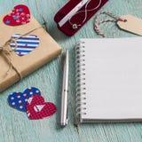 在牛皮纸,妇女的在天鹅绒囊的首饰链子的情人节礼物和清洗蓝色木表面上的空白的笔记薄 免版税库存图片
