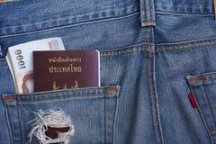 在牛仔布斜纹布的口袋的护照和金钱钞票 免版税库存图片