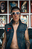 在牛仔布背心和太阳镜的纹身花刺大师在演播室 免版税库存照片
