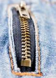 在牛仔布背景的金属拉链 库存图片