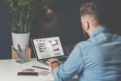 在牛仔布衬衣的年轻有胡子的商人在办公室坐在桌上和使用有图的,图表膝上型计算机 库存照片