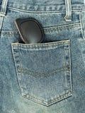 在牛仔裤口袋的太阳镜 库存照片