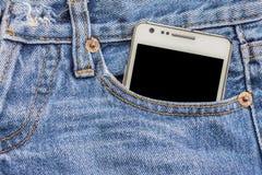 在牛仔裤口袋的白色电话 免版税库存图片