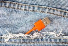 在牛仔裤口袋的红色USB缆绳 免版税库存照片