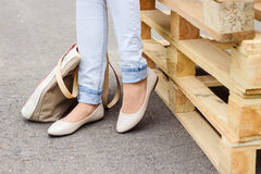 在牛仔裤和平的鞋子的妇女的腿 库存照片