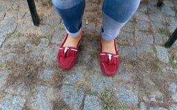 在牛仔裤和红色游手好闲者的妇女腿 库存照片