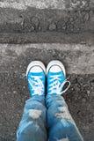 在牛仔裤和蓝色鞋子的脚在街道边缘站立 免版税图库摄影