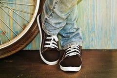 在牛仔裤和运动鞋的脚 免版税库存图片