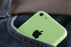 在牛仔裤的一个口袋的苹果计算机iPhone 5C绿色 库存图片